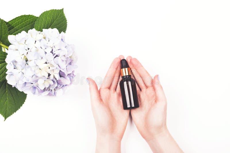 血清瓶或精油在妇女手上 库存图片