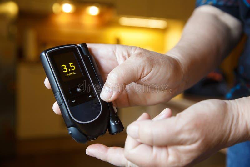 血糖过低的糖尿病耐心测试她的糖水平 库存图片