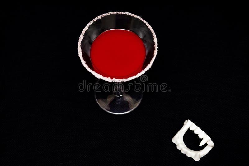 血腥的万圣节吸血鬼的饮料和尖牙,在黑色背景上,留有复制文本的空间……血淋淋的万圣节吸血é 库存照片