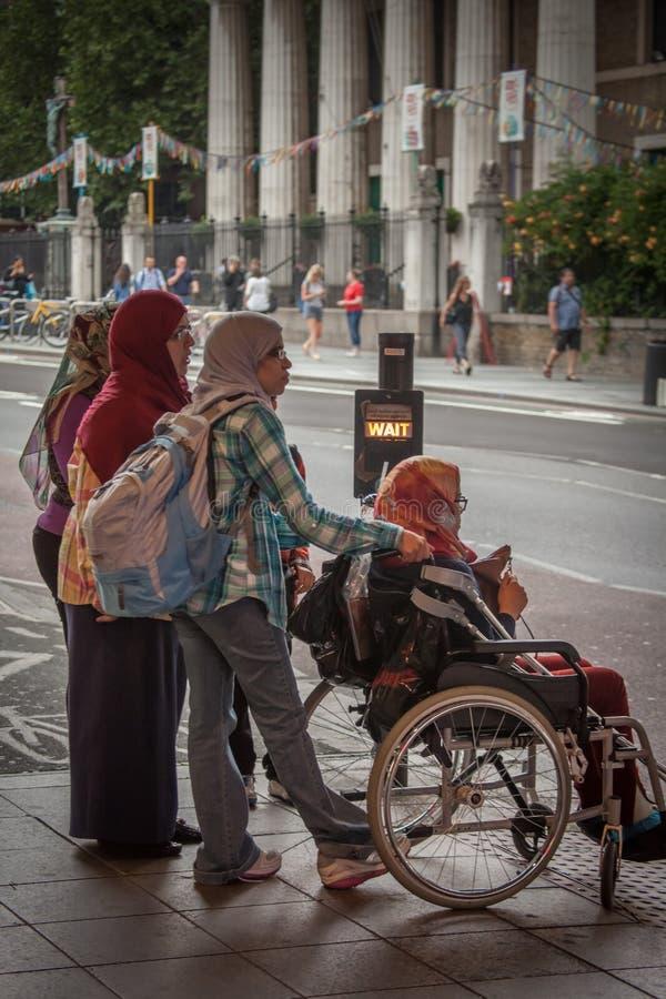 行人交叉路的回教妇女 库存图片