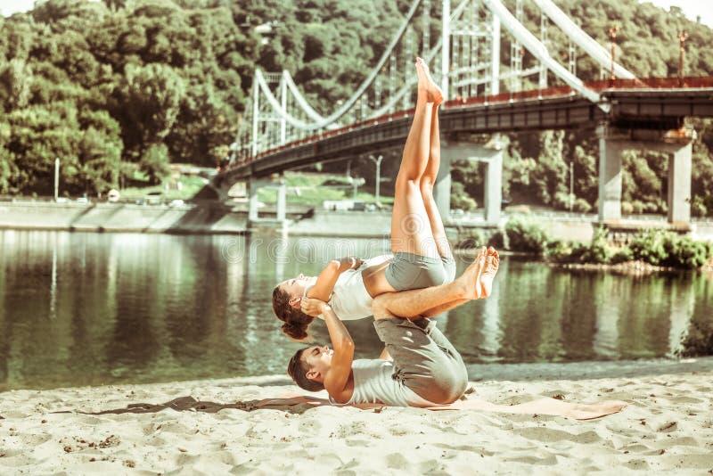 行使与他的瑜伽伙伴的年轻被晒黑的人 图库摄影