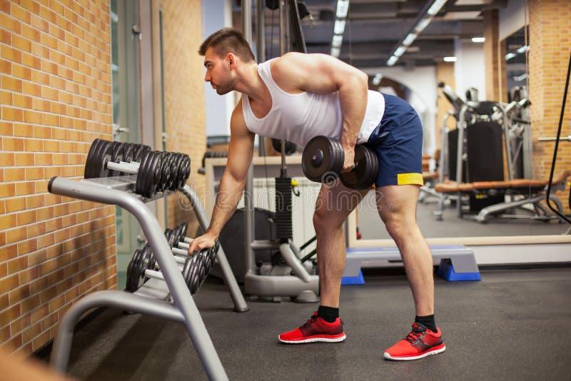 行使与哑铃的年轻人在健身房 免版税库存图片