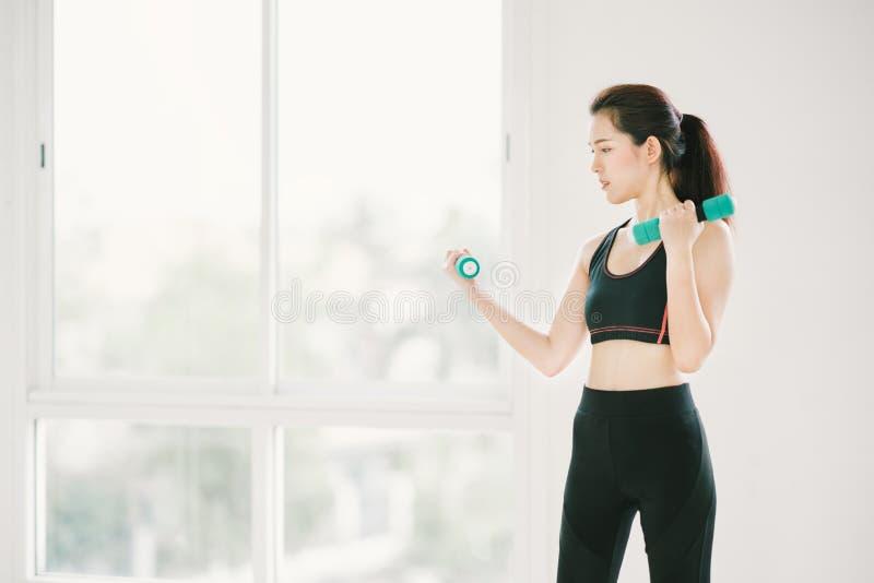 行使与哑铃的性感的亚裔女孩在与拷贝空间、体育和健康生活方式概念的健身健身房 库存图片