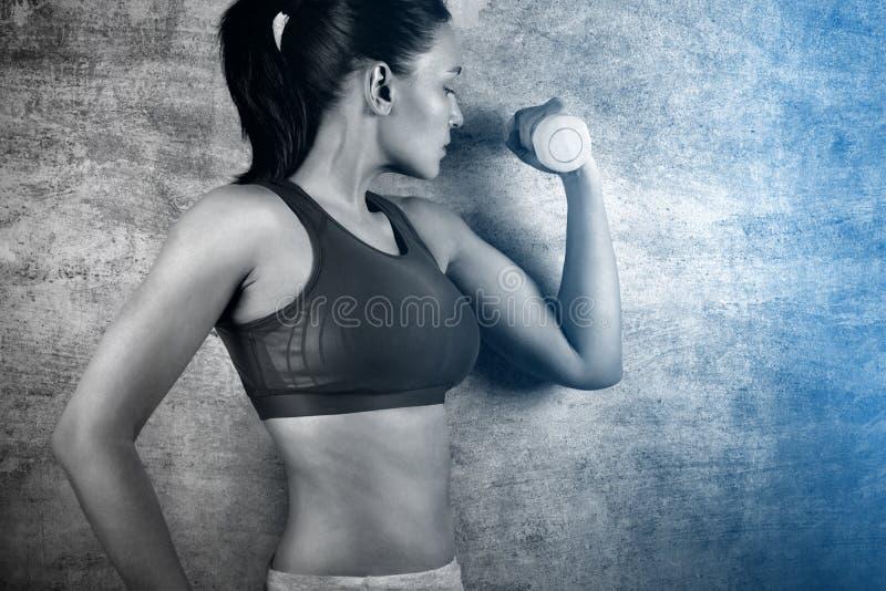 行使与在一个混凝土墙的背景的重量的适合的妇女在健身房的 概念健康生活方式 免版税图库摄影