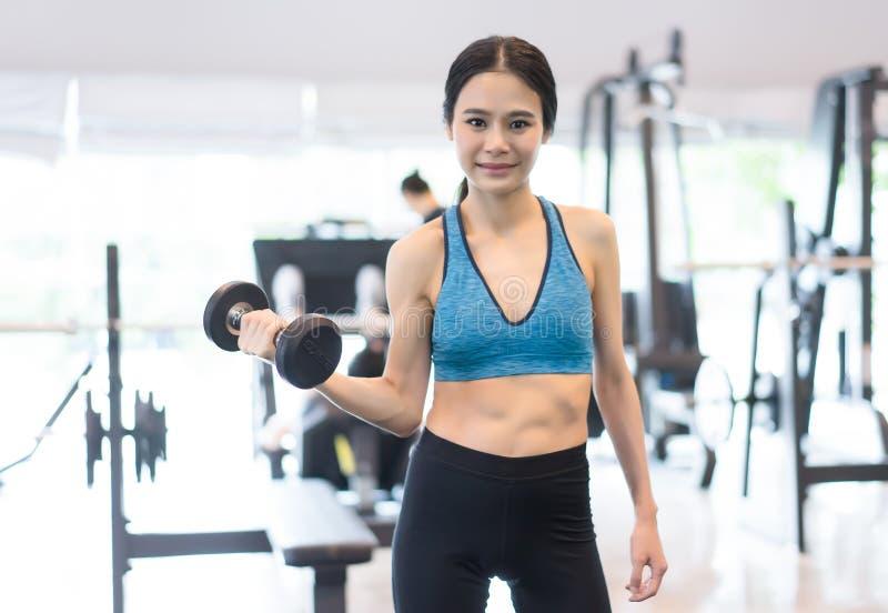 行使与在健身房的哑铃, F的年轻快乐的微笑的妇女 免版税图库摄影