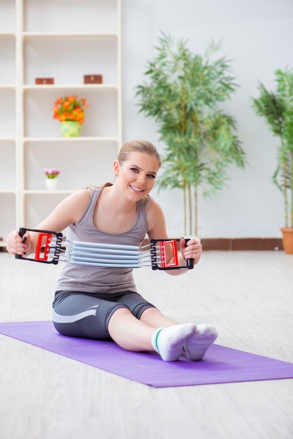 行使与在健身房的抵抗带的少妇 免版税库存图片