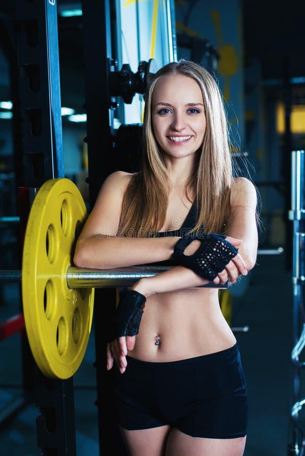 行使与在健身房的杠铃的可爱的运动的妇女 休息在体育锻炼以后的美丽的健身女孩行使 免版税库存照片