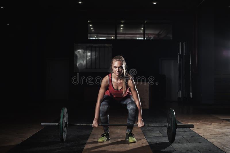 行使与在健身房的杠铃的坚强的白肤金发的妇女 免版税库存照片