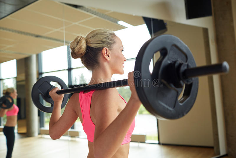 行使与在健身房的杠铃的运动的妇女 免版税库存图片