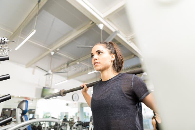行使与在健身房的空的杠铃的运动妇女 免版税图库摄影