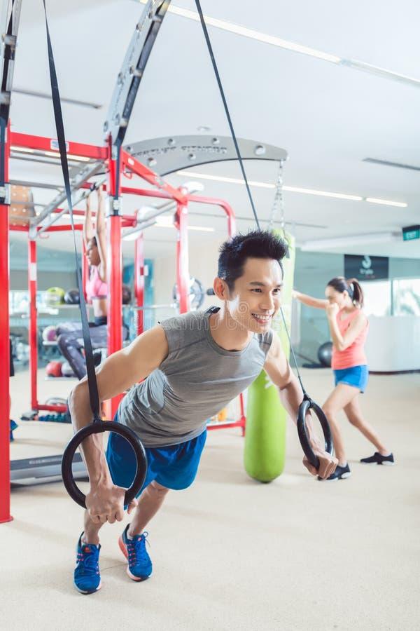 行使与在时髦健身的体操圆环的适合的年轻人 免版税库存照片