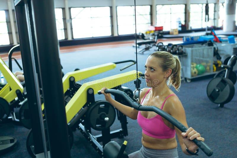 行使与拉特折叠式的机器的女运动员在健身演播室 免版税库存照片