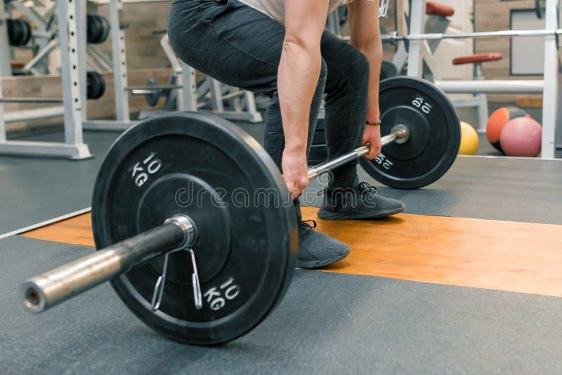 行使与杠铃的人的胳膊和腿特写镜头在体育健身房 运动员,体型,训练,举重,锻炼 免版税库存照片