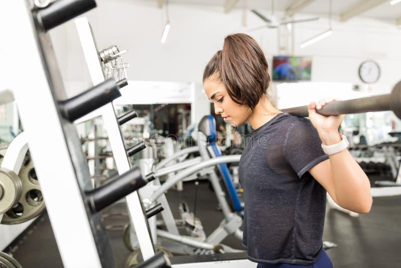 行使与空的杠铃的妇女在健身房类期间 免版税库存图片