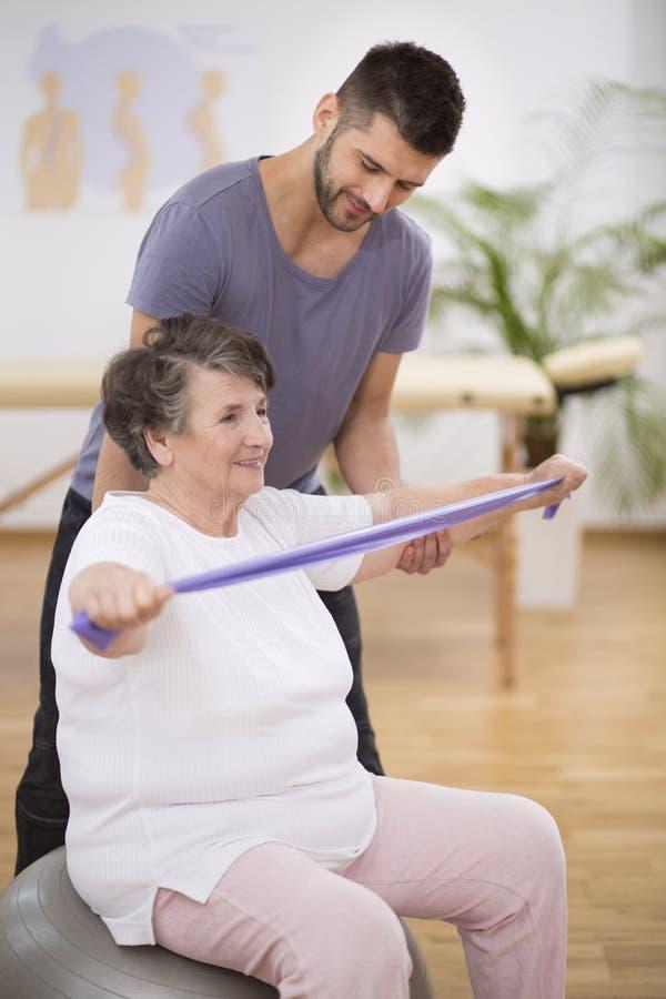 行使与舒展的年长妇女有她的生理治疗师的磁带 免版税图库摄影