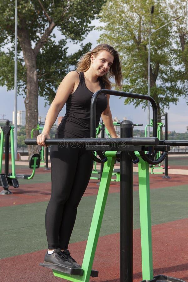 行使与运动器材的坚强的妇女在公园 训练衣服的运动员女孩解决在室外健身房的 免版税库存图片