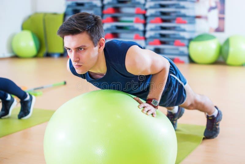 行使与适合球锻炼臂跑训练三头肌和二头肌的适合的人做俯卧撑 库存照片