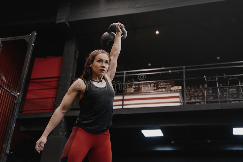 行使与kettlebell的坚强的crossfit妇女在健身房 女性做的功能训练 库存图片