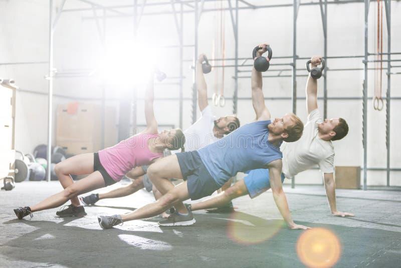 行使与kettlebells的人们在crossfit健身房 免版税库存照片