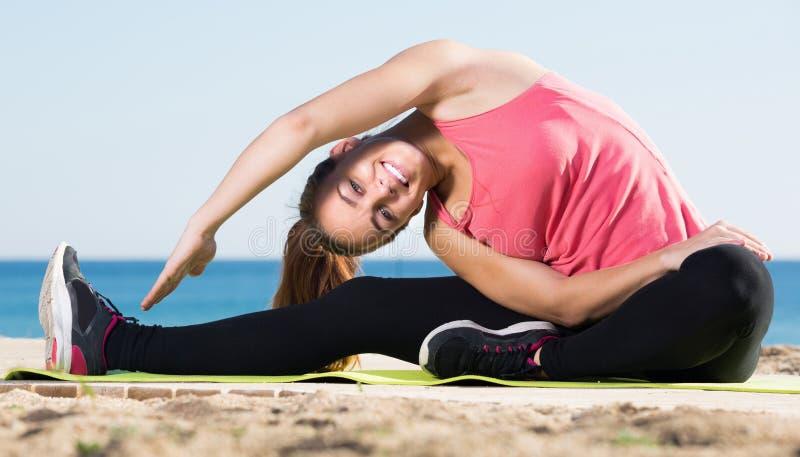 行使体操行动的愉快的美丽的妇女 免版税库存图片