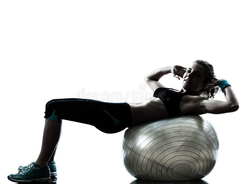 行使健身球锻炼剪影的妇女 免版税库存照片