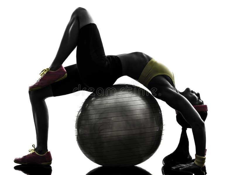 行使健身球锻炼剪影的柔软妇女 免版税库存照片