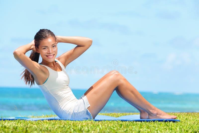 行使健身的妇女做仰卧起坐外面 免版税图库摄影