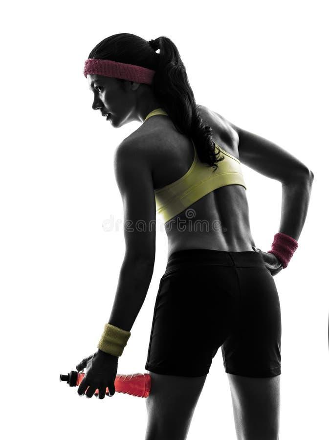 行使健身的妇女拿着能量饮料剪影 免版税库存图片