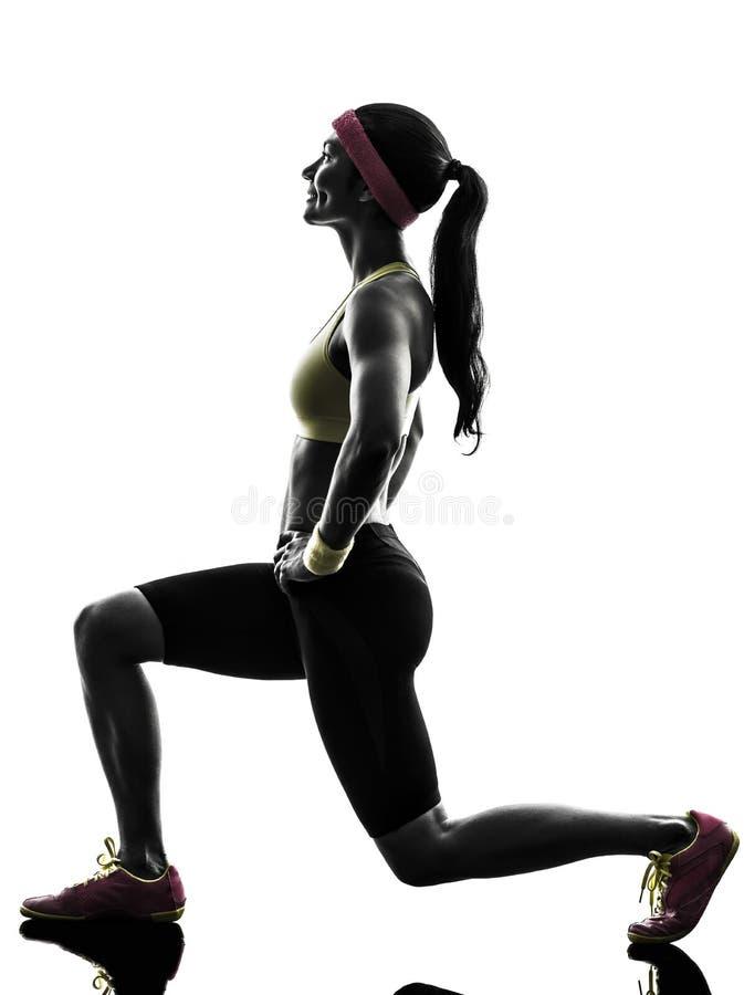 行使健身锻炼刺蹲下的剪影的妇女 免版税库存照片