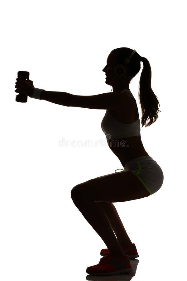 行使健身锻炼的一名妇女刺蹲下的重量tra 免版税库存图片