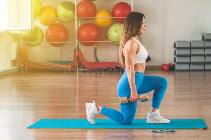 行使十字架的健身妇女适合举行哑铃 健身辅导员在体育室背景中 免版税图库摄影