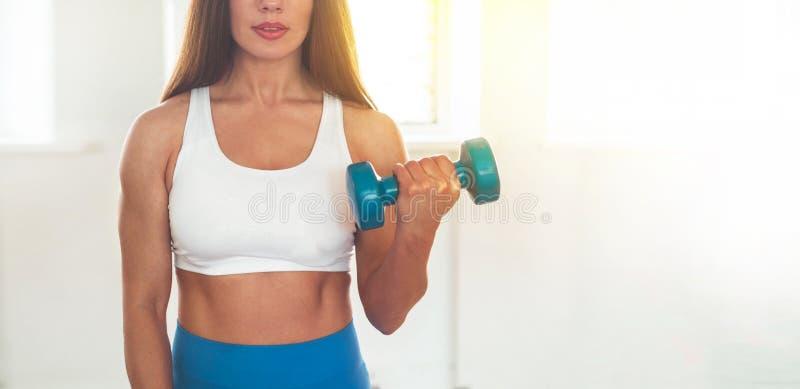 行使十字架的健身妇女适合举行哑铃 健身辅导员在体育室背景中 免版税库存照片
