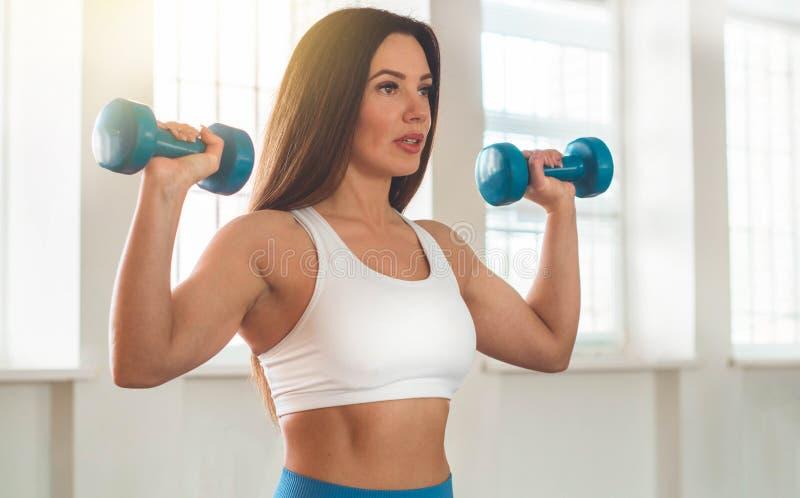 行使十字架的健身妇女适合举行哑铃 健身辅导员在体育室背景中 免版税库存图片