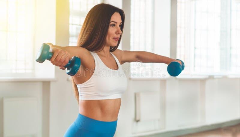 行使十字架的健身妇女适合举行哑铃 健身辅导员在体育室背景中 库存照片