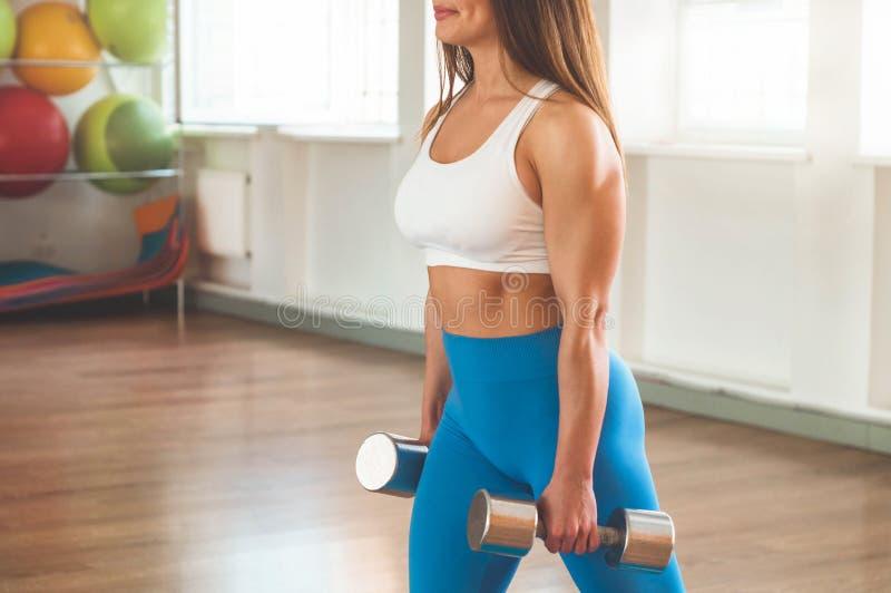 行使十字架的健身妇女适合举行哑铃 健身辅导员在体育室背景中 库存图片