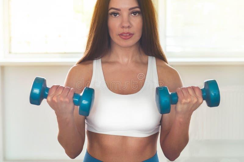行使十字架的健身妇女适合举行哑铃 健身辅导员在体育室背景中 图库摄影