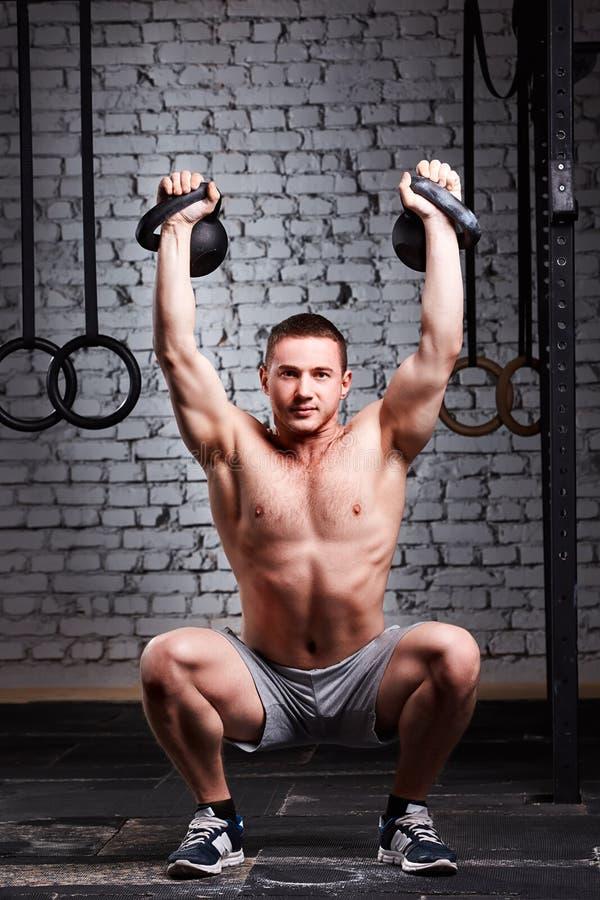 行使十字架的年轻健身运动员符合kettlebell对在健身房的砖墙 免版税图库摄影