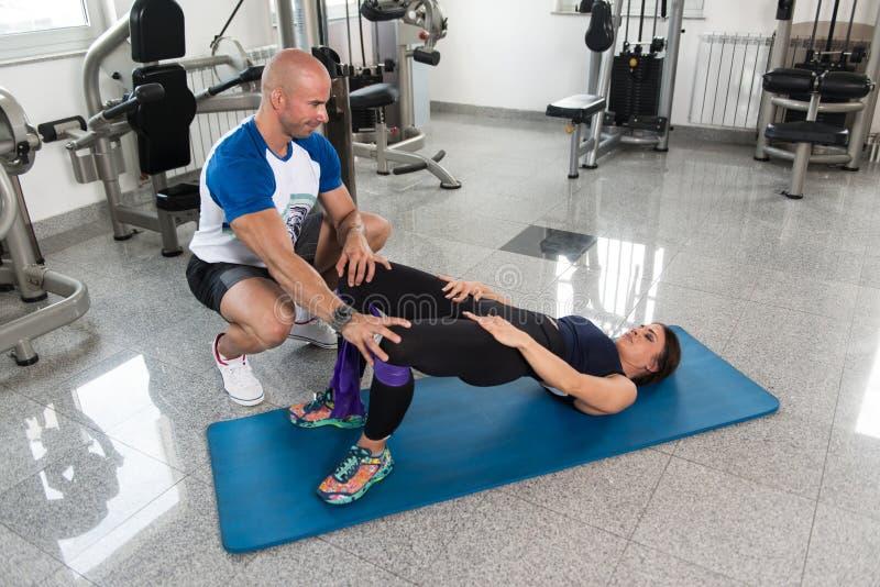 行使在与抵抗带的健身房的夫妇 图库摄影