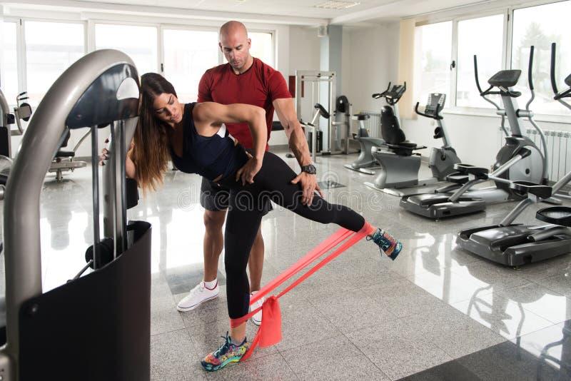 行使在与抵抗带的健身房的夫妇 库存照片