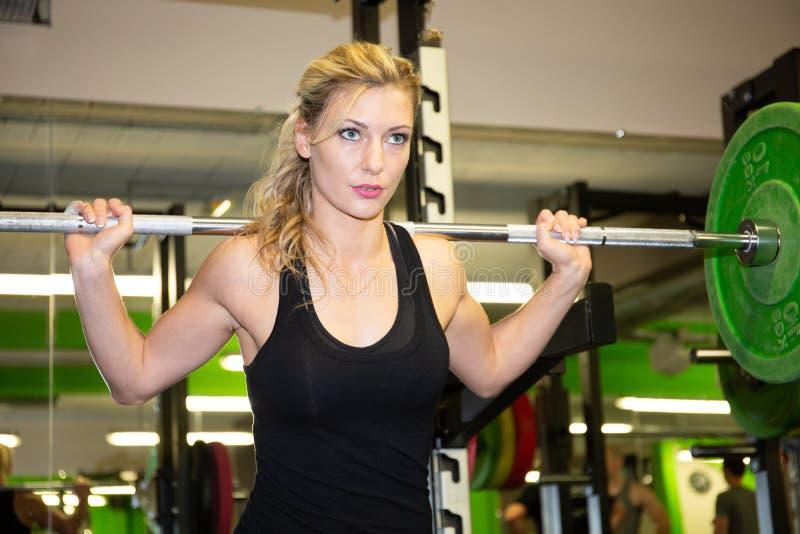 行使在与杠铃重量的健身房的健身白肤金发的妇女 库存照片
