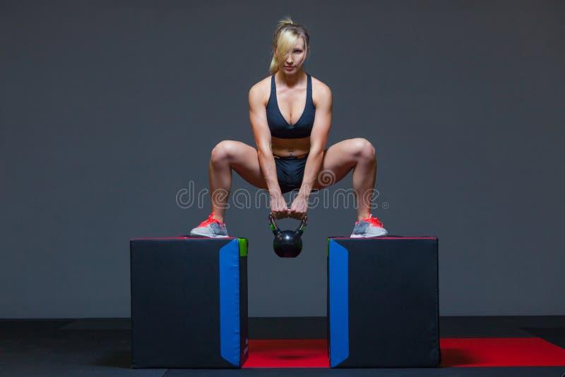 行使在与kettlebell重量的一间健身房的妇女,在立方体 免版税库存照片