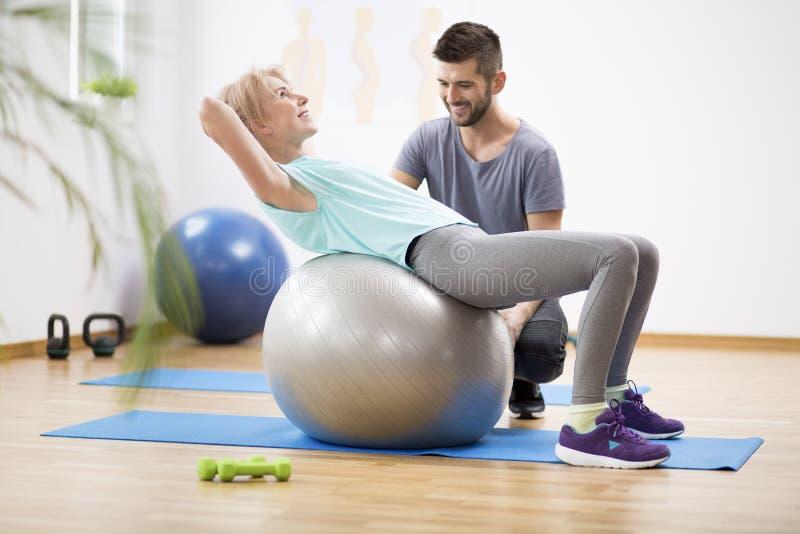 行使在体操球的中年白肤金发的妇女在与生理治疗师的会议期间 图库摄影