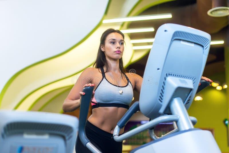 行使在健身健身房有氧运动省略步行者教练员锻炼的适合的妇女 图库摄影