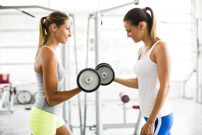 行使在健身房的少妇举的重量 库存图片