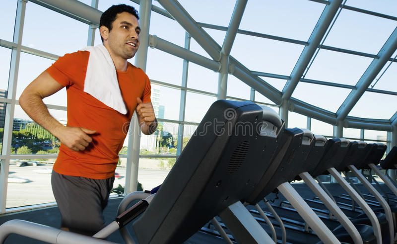 行使在健身房的踏车的人 图库摄影