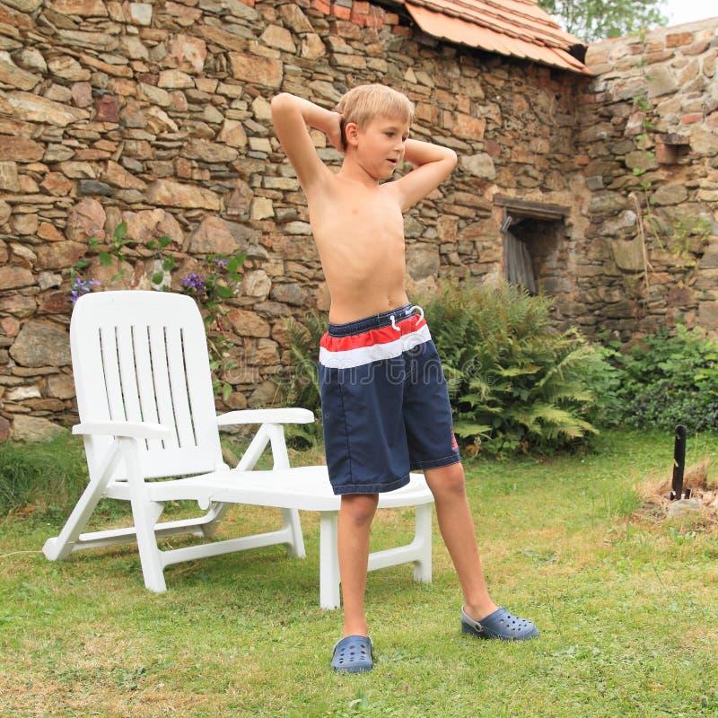 行使在庭院懒人前面的男孩 免版税库存照片