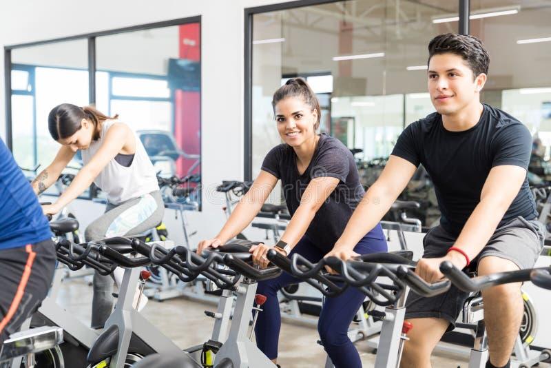 行使在有朋友的转动的自行车的微笑的妇女 免版税库存图片