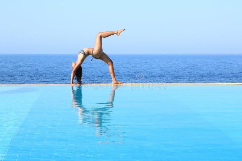 行使在水池边缘的年轻女人瑜伽由海 免版税库存照片