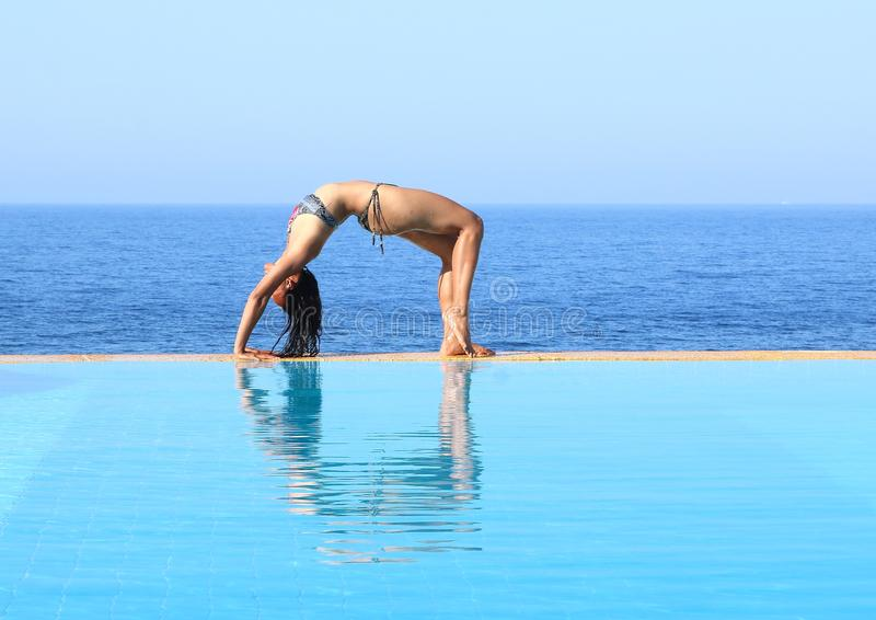 行使在水池边缘的年轻女人瑜伽由海 库存照片
