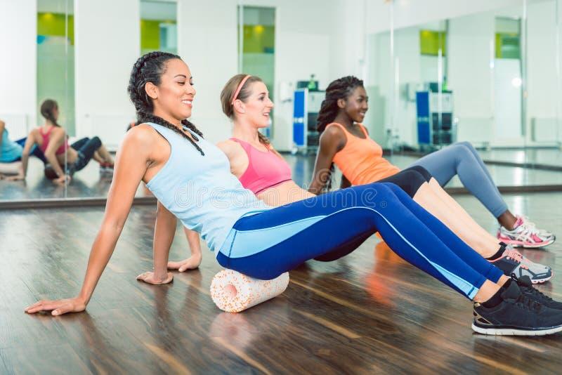 行使在泡沫路辗的适合的美丽的妇女在小组锻炼类期间 免版税库存图片